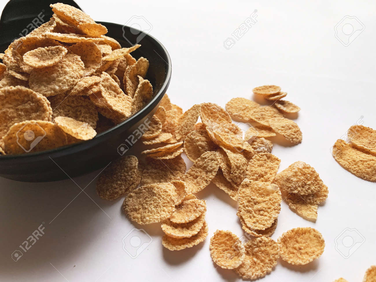 Multi-cereal flakes in a black cup with scattered flakes on white background. Closeup. - 169603129