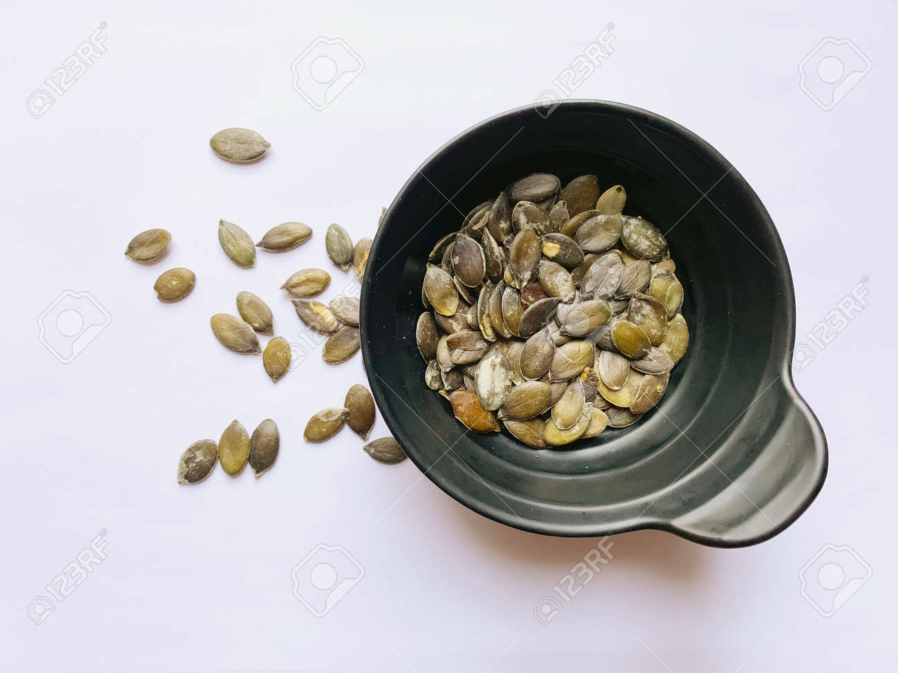 Styrian pumpkin seeds in a black cup and scattered on a white background. View from above. - 169603136
