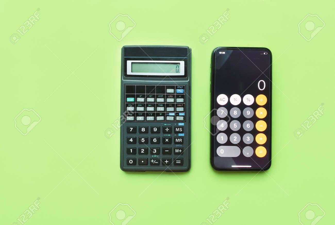 Digital calculator and calculator in smartphone on green background. technology development. - 169603135