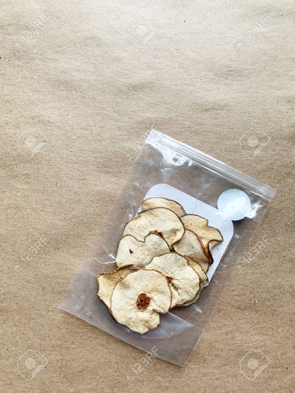 Pieces of dried pear in plastic packaging on craft paper background. - 169603142