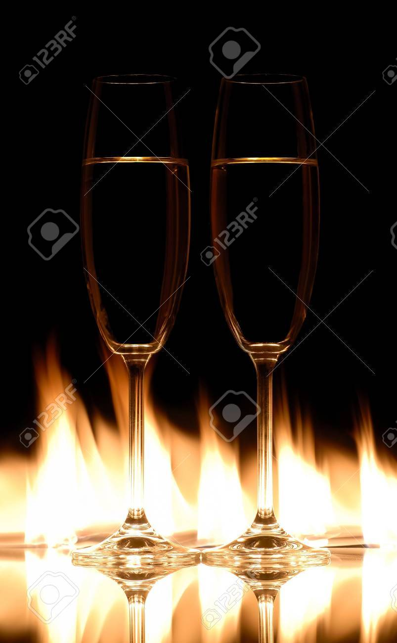 Two champagne glasses on fire with black background Stock Photo - 3231988
