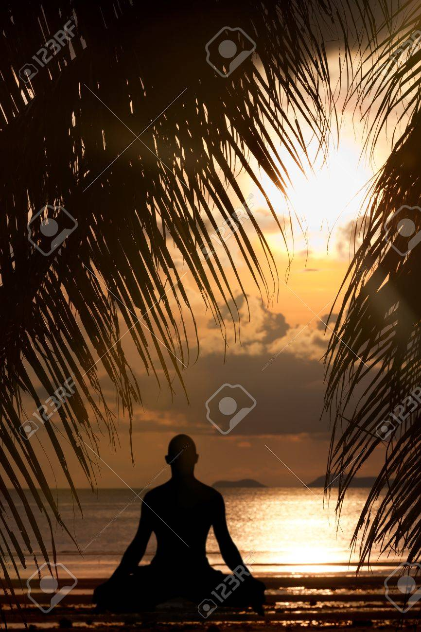 Man silhouette doing yoga exercise at sunset beach Stock Photo - 12520737