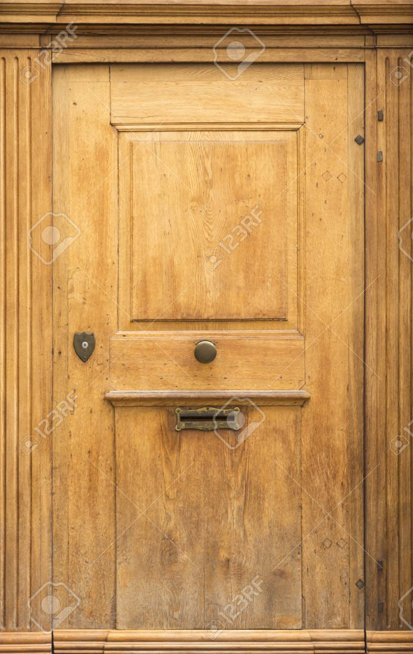 Old Light Brown Wooden Door With Round Metal Knob And Mail Box Slit. Stock  Photo
