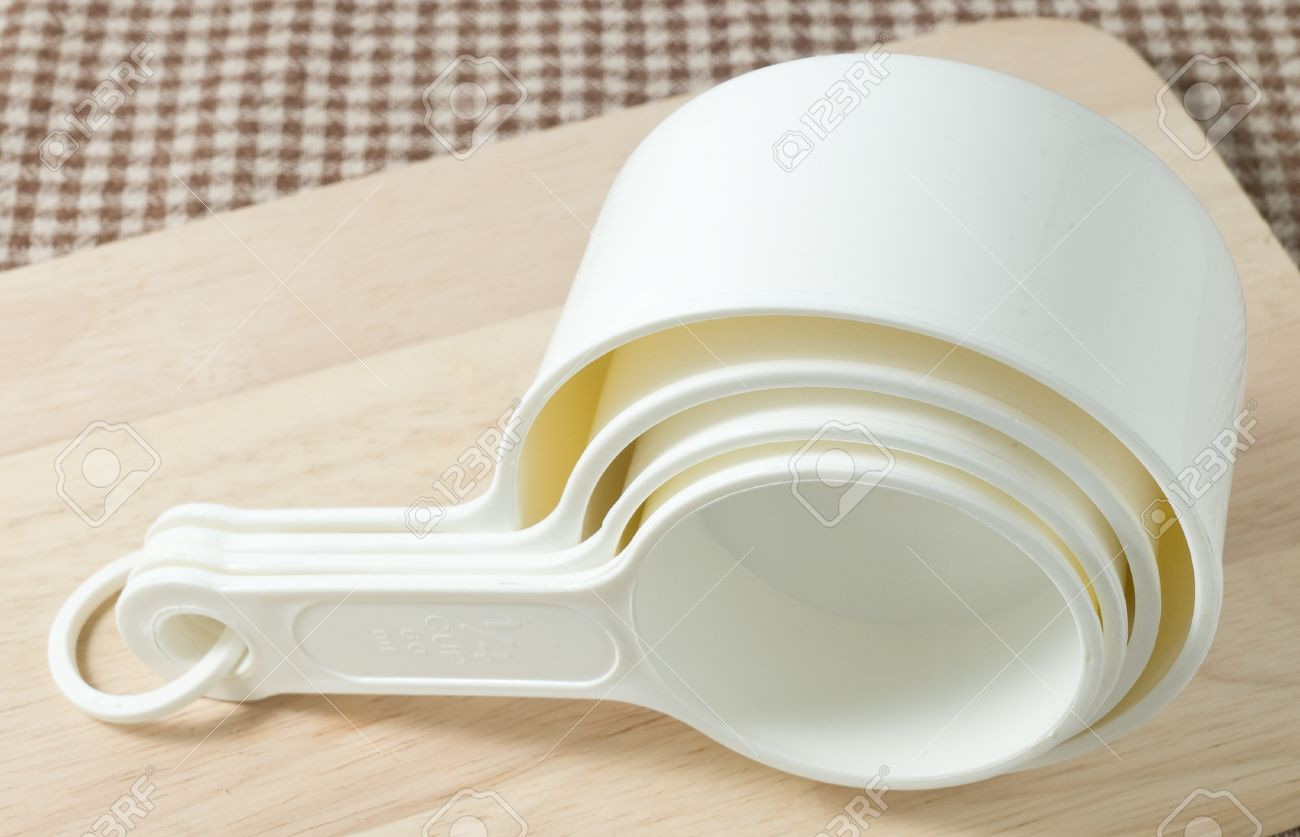 Delicieux Kitchen Tools And Equipment, White Plastic Measuring Cups In Different  Sizes On Wooden Cutting Board