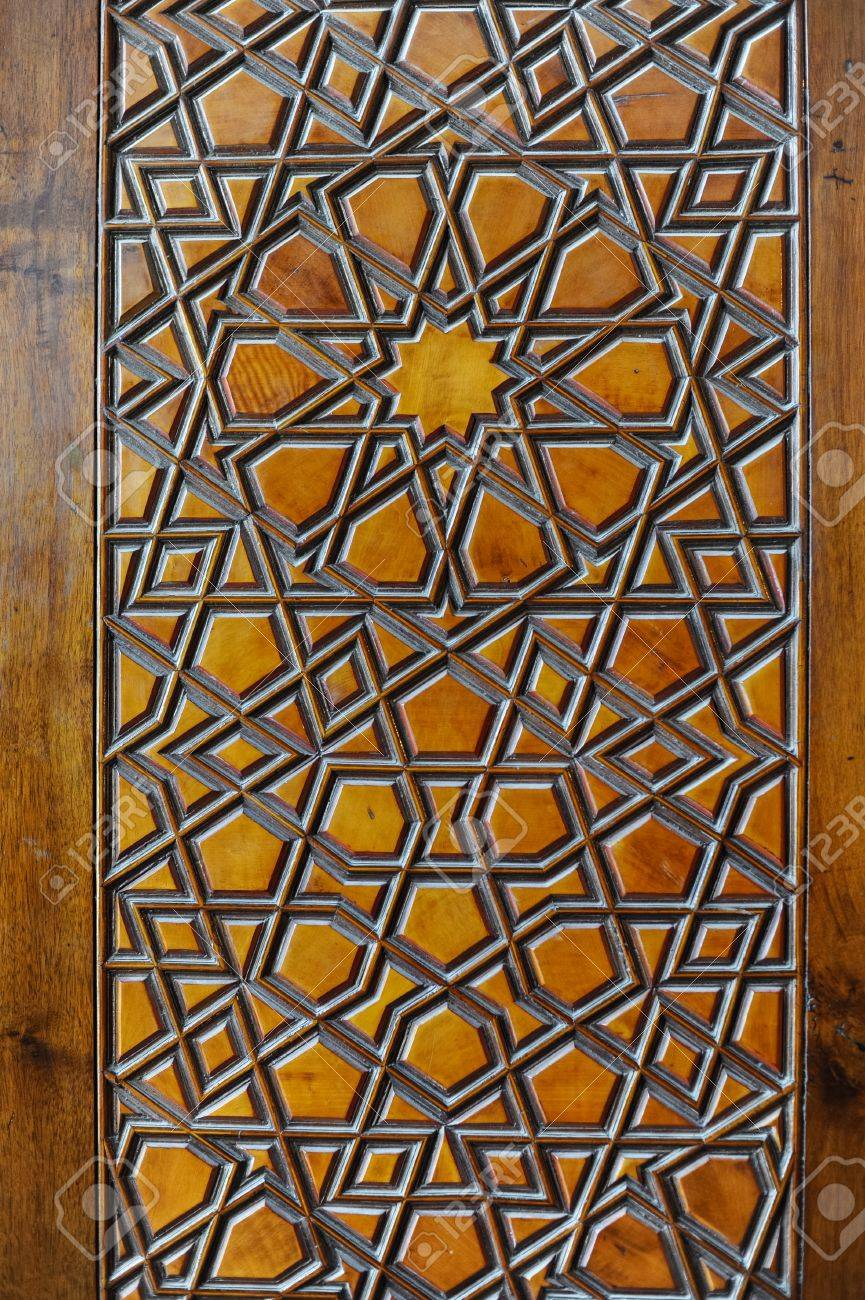 Islamic carvings on wooden surface of a golden colored window