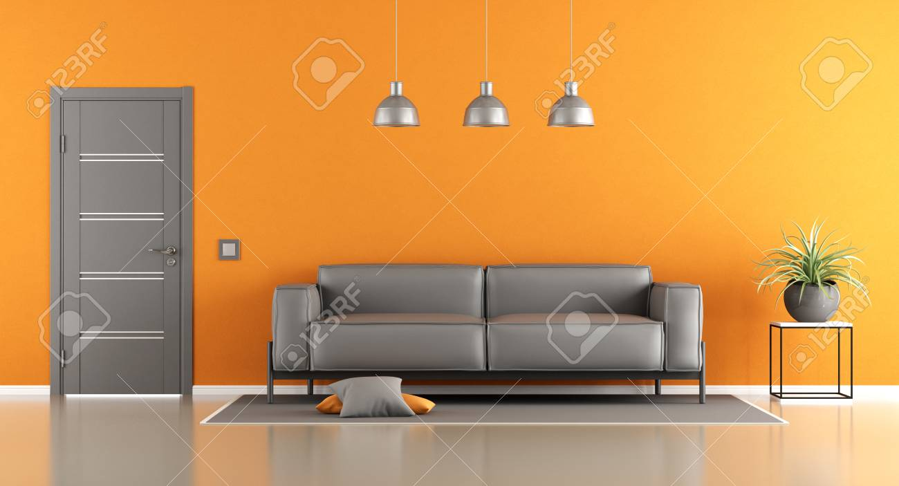 Gray and orange living room with modern sofa and closed door..