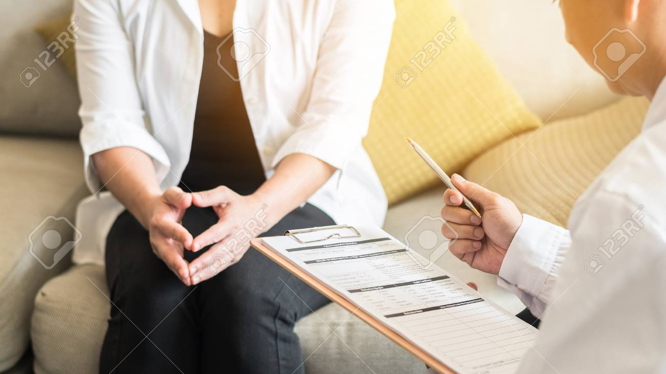 Doctor (gynecologist or psychiatrist) consulting and examining woman patient's health in medical clinic or hospital health service center - 111200738