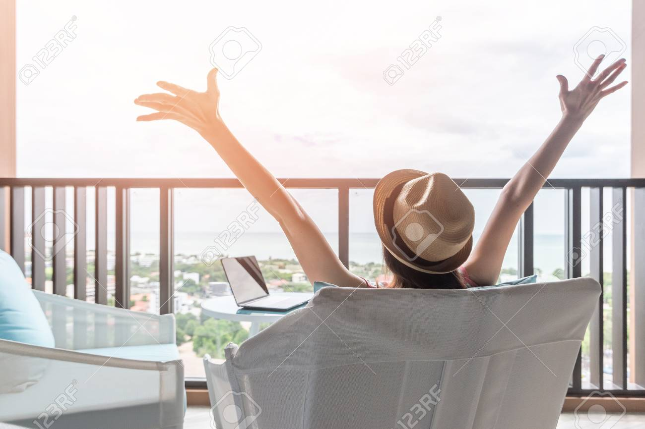 Life balance and summer holiday vacation concept with happy woman taking a break, celebrating successful work done, casually resting in luxury resort hotel workplace with computer pc laptop on desk - 112390525