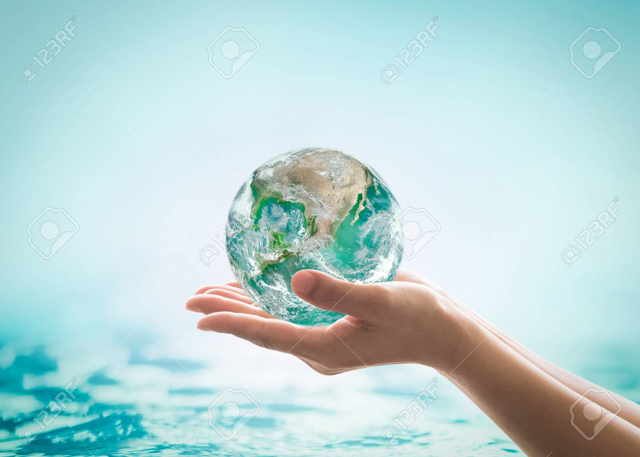 World ocean day, saving water campaign, sustainable ecological ecosystems concept with green earth on woman's hands on blue sea background - 112436671
