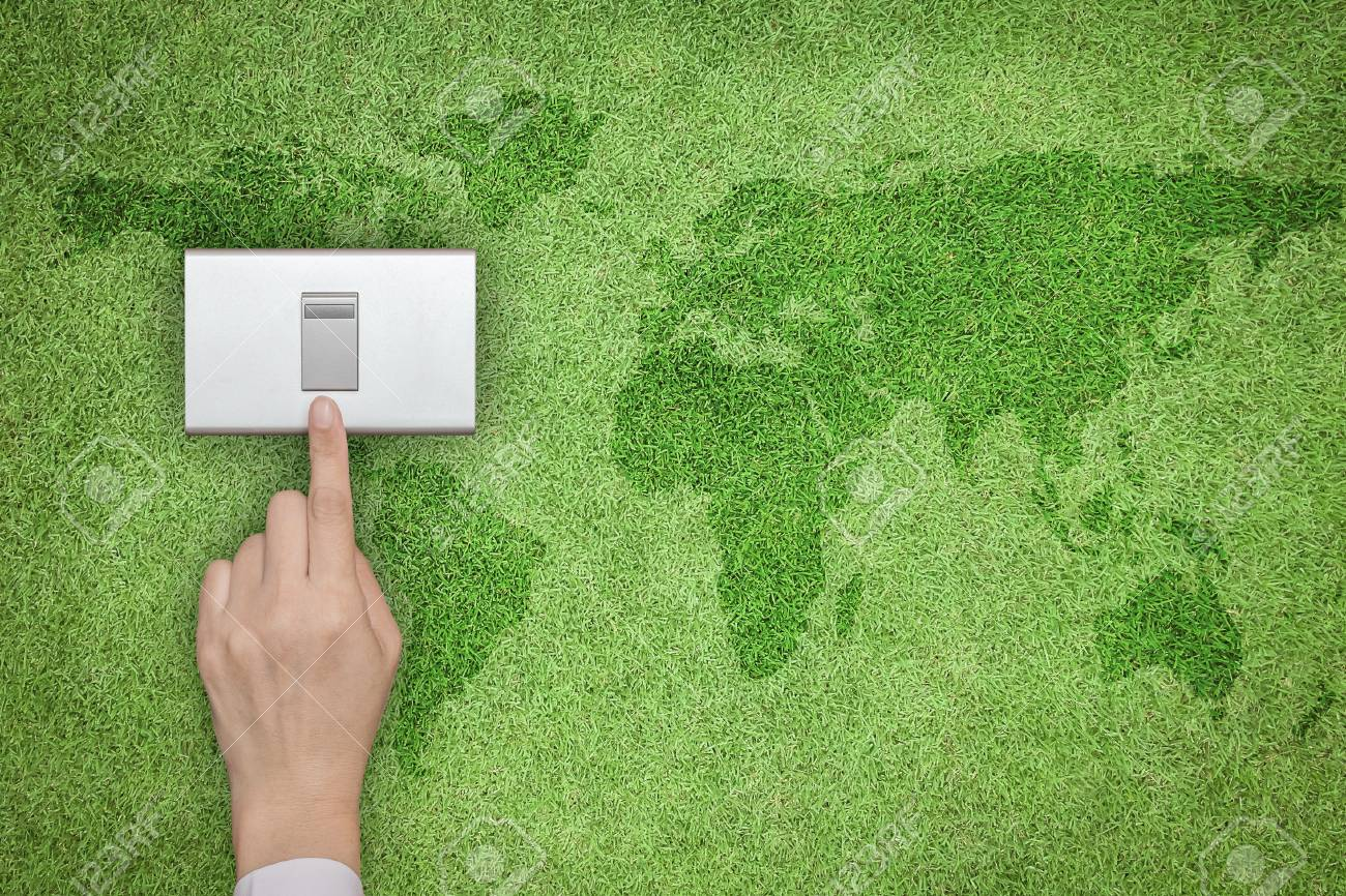 Energy saving and ecological friendly concept with hand turning off switch on green grass lawn with world map - 112511363