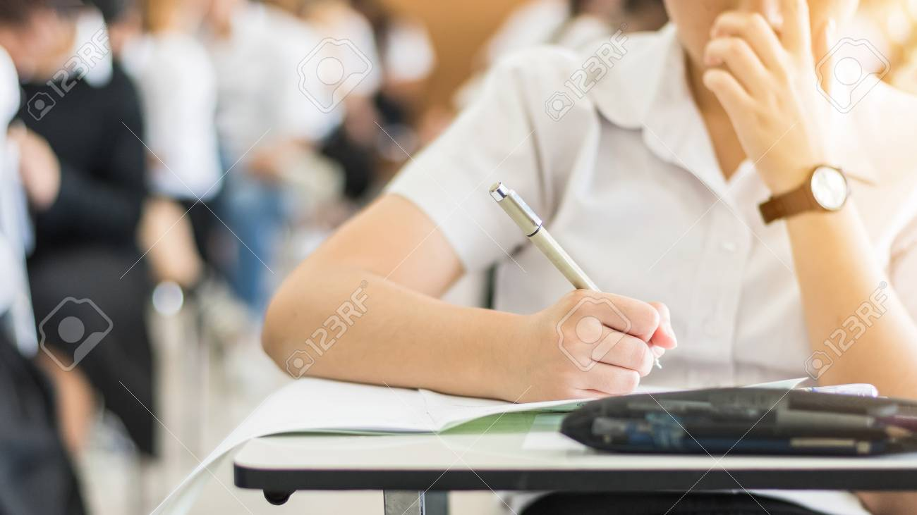 School student's taking exam, thinking hard, writing answer in classroom for educational university admission test and world literacy day concept - 116069121