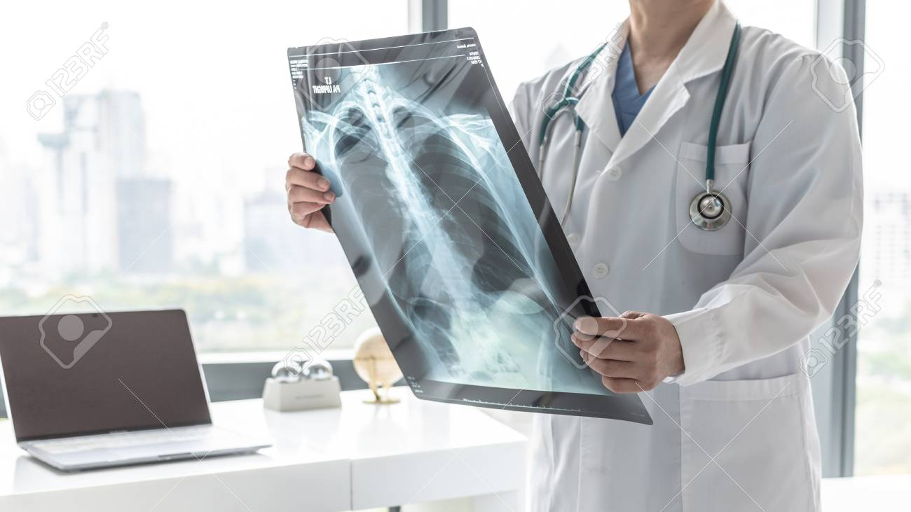 Doctor with radiological chest x-ray film for medical diagnosis on patient's health on asthma, lung disease and bone cancer illness, healthcare hospital service concept - 119068744