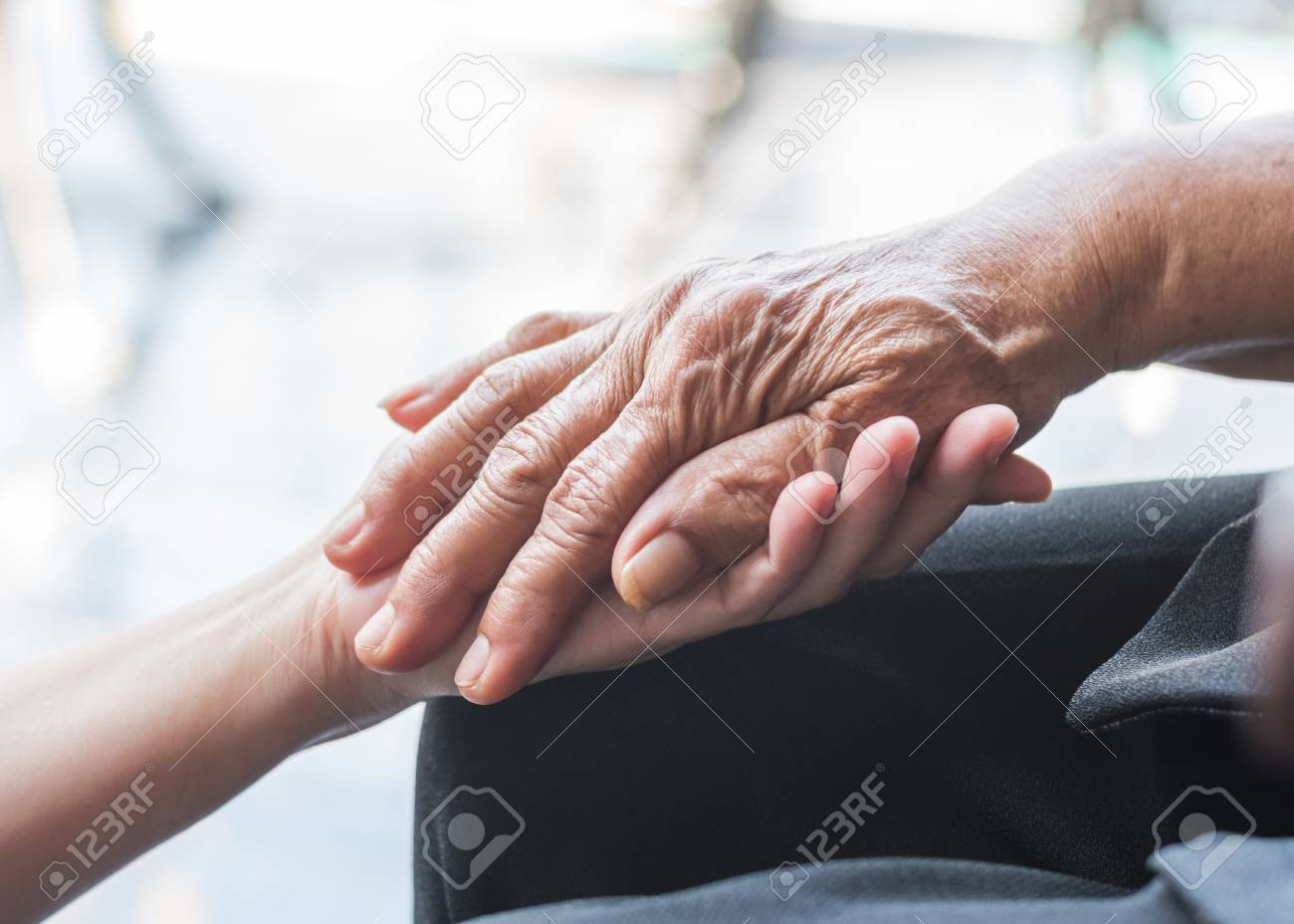 Disability awareness day and aging society concept with Parkinson disease patient or elderly senior person in support of nursing family caregiver's hand - 121248548