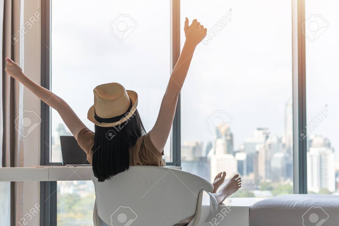 Work-life balance, work and travel lifestyle relaxation of young freelancer Asian working woman celebrating healthy living happily resting in comfort luxurious hotel guest room with peace of mind - 121253129