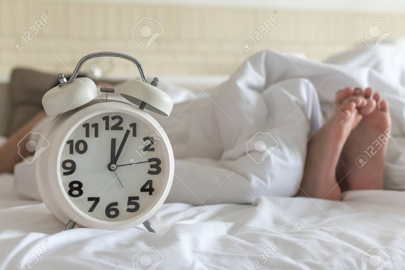 Bedtime sleep with alarm clock at noon or midnight time on bed..