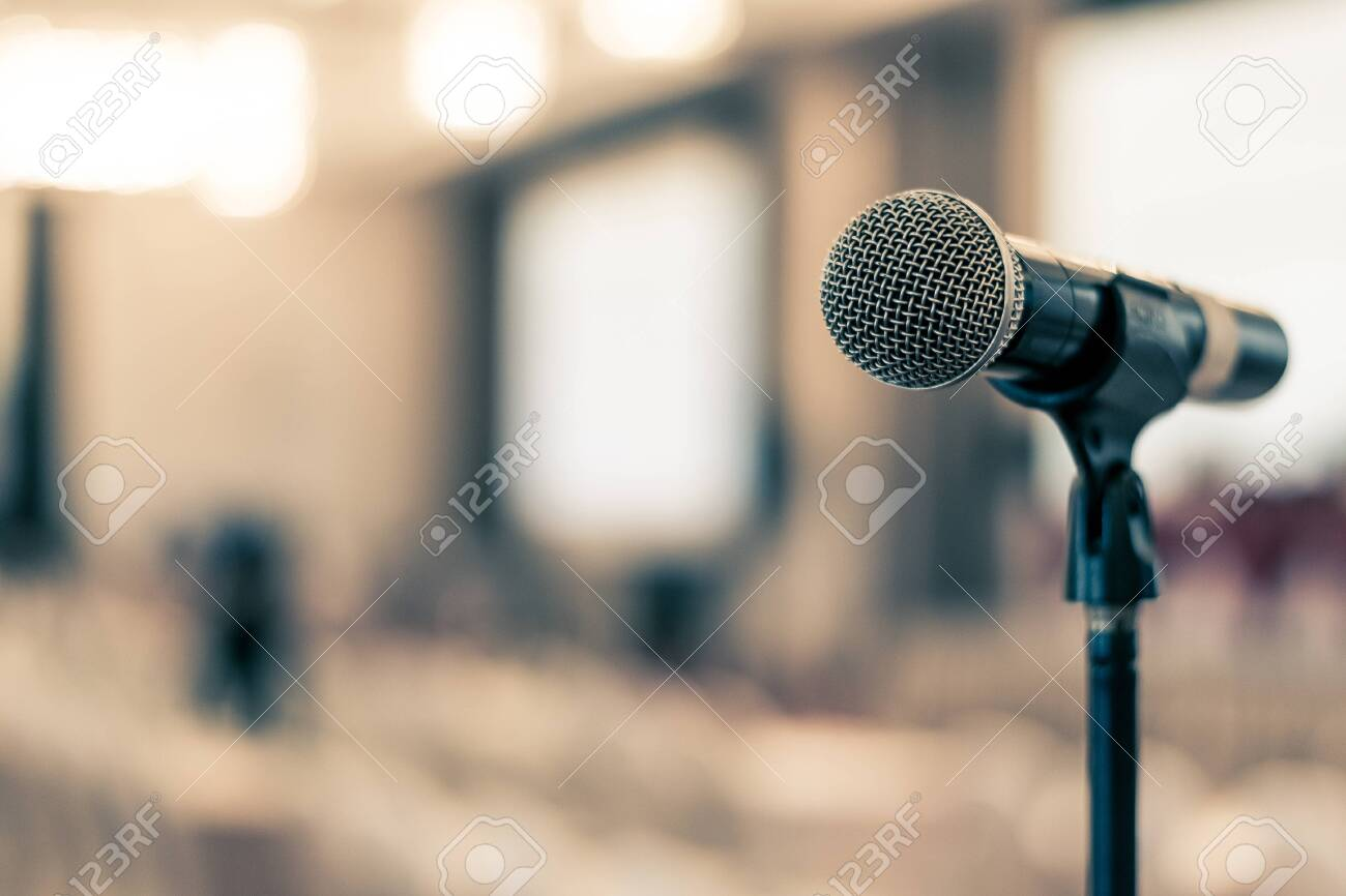 Microphone voice speaker in business seminar, speech presentation, town hall meeting, lecture hall or conference room in corporate or community event for host or public hearing - 121950803