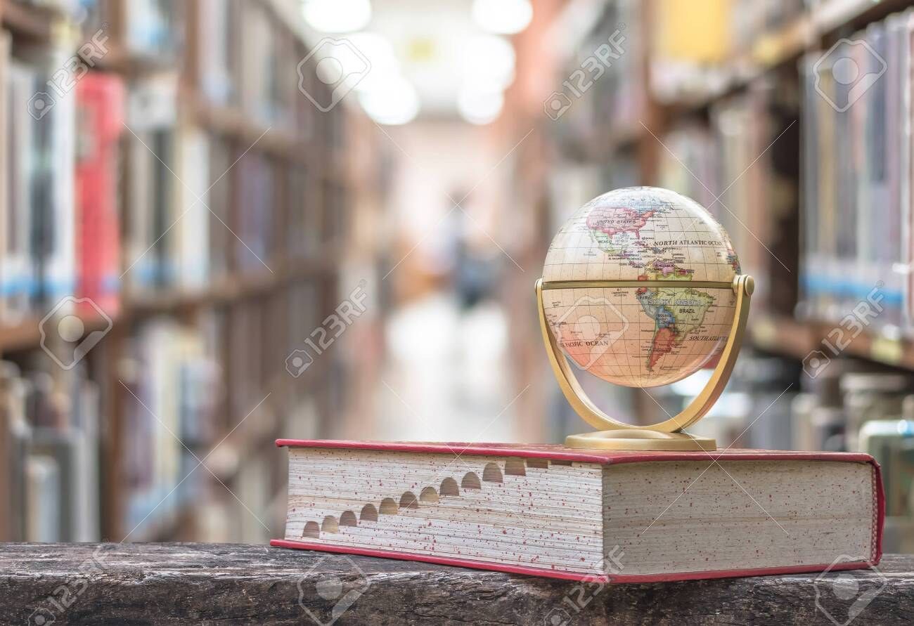 FEBRUARY 7, 2018 - BANGKOK, THAILAND: Globe model on textbook, or dictionary on table in school or university library educational resource for knowledge - 131563183