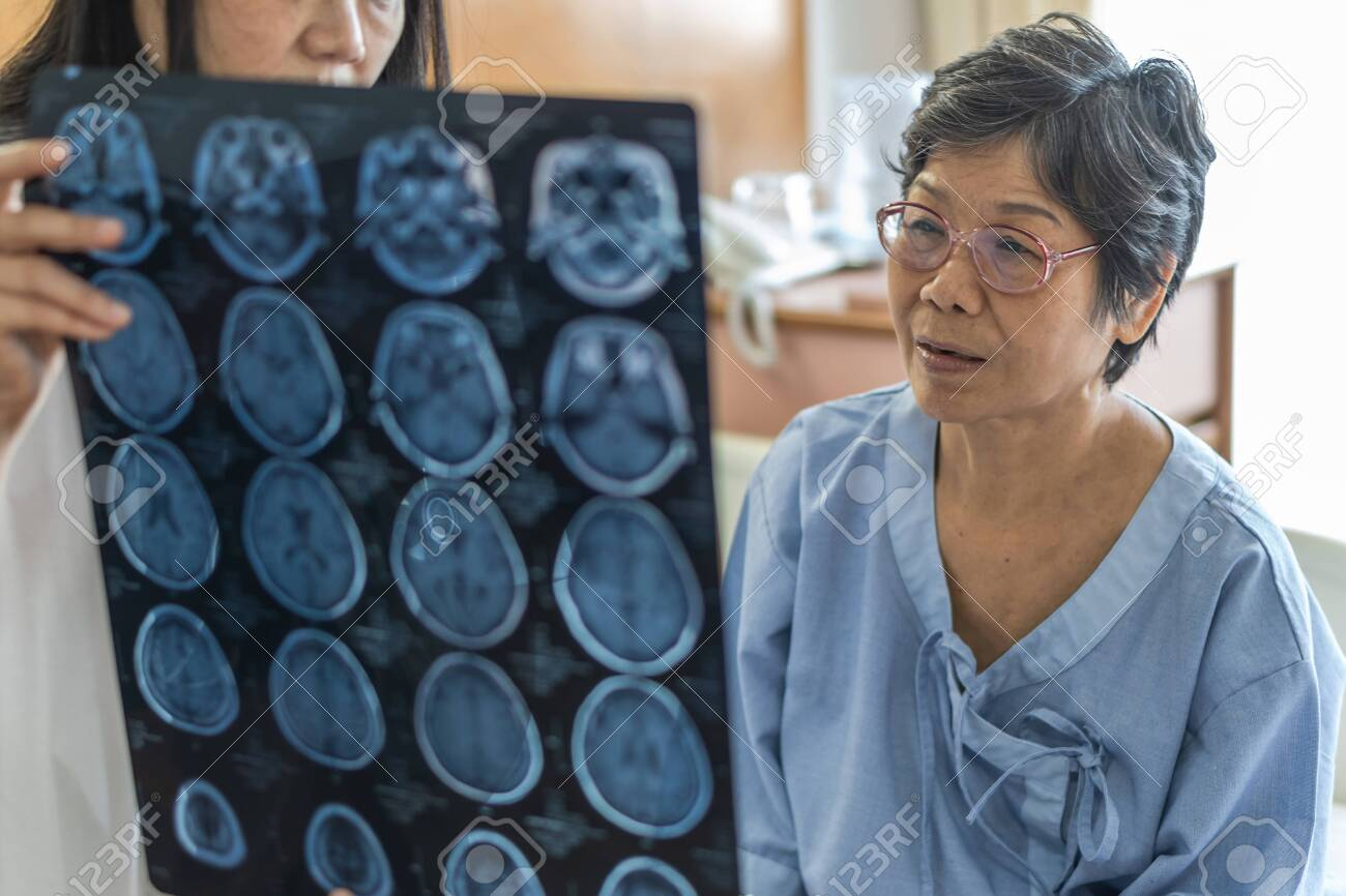 Brain disease diagnosis with medical doctor diagnosing elderly ageing patient neurodegenerative illness problem seeing Magnetic Resonance Imaging (MRI) film for neurological medical treatment - 132157460