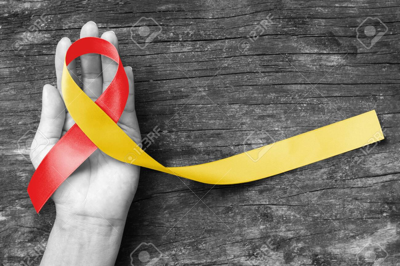World hepatitis day and HIV/ HCV co-infection awareness with red yellow ribbon on person's hand support and old aged wood - 133812657