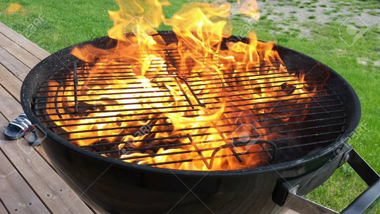 Hot vivid flames on coal fueled barbeque grill in summer closeup