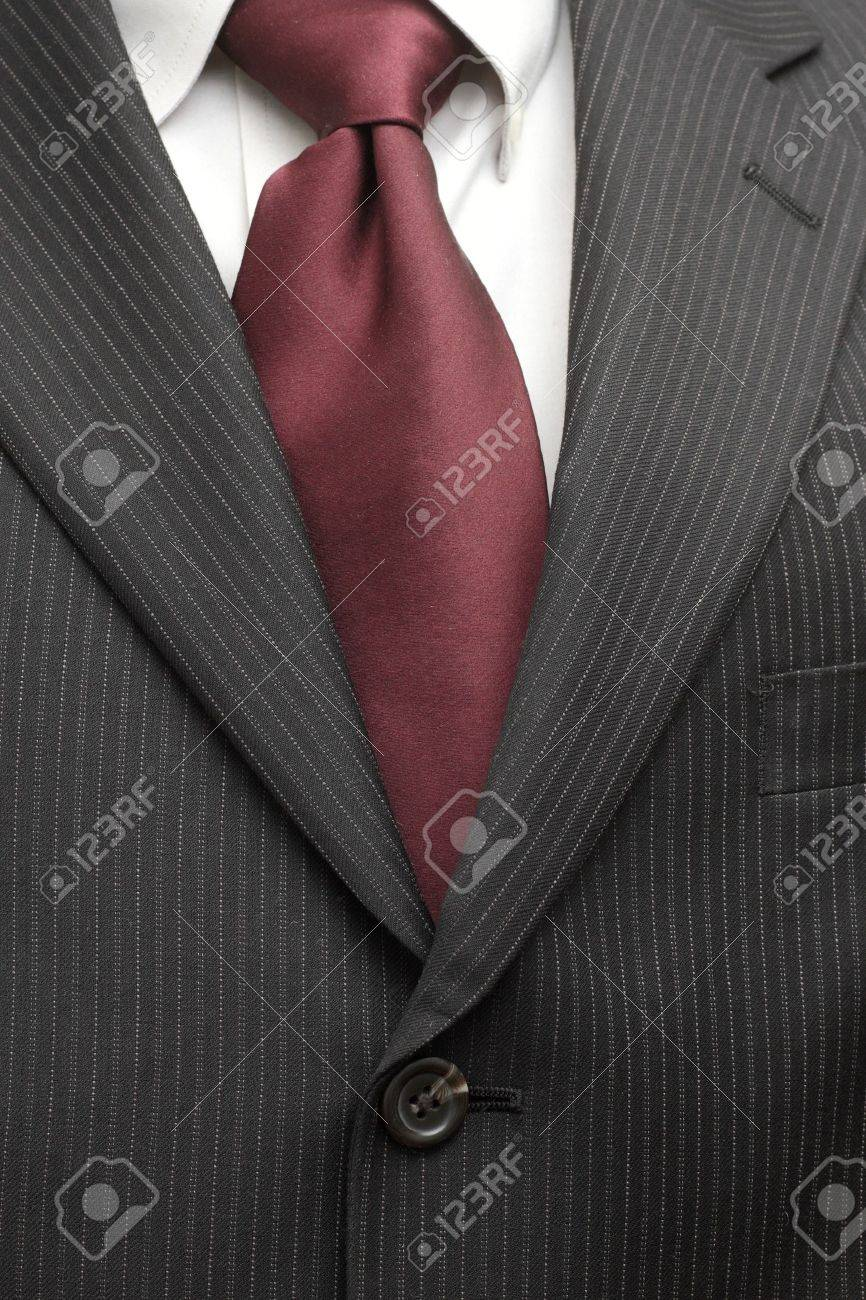 A pinstriped charcoal grey wool men's business suit with a silk tie and plain shirt. - 11323635