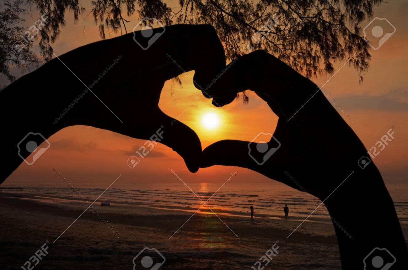 La Salida Del Sol En El Marco Del Corazón De La Mano En La Playa ...