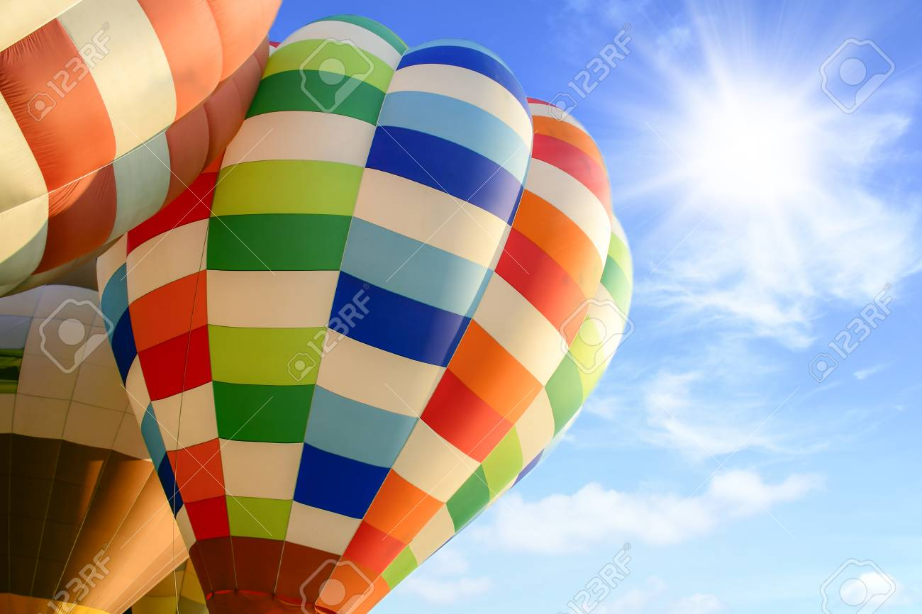Colorful hot air balloon over bright sky with clouds. Hot air balloon and blue sky - 125660461