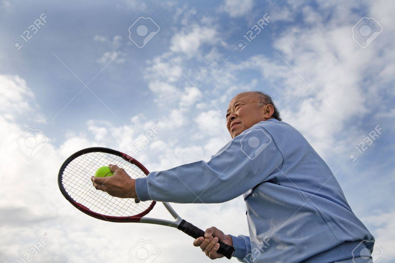 A shot of a senior asian man playing tennis Stock Photo - 2851316