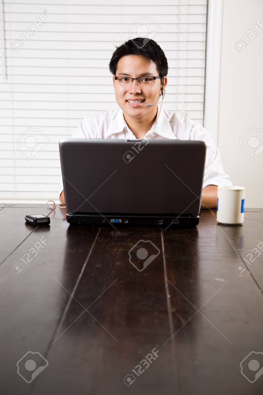 An asian entrepreneur talking on the phone and working on his laptop Stock Photo - 3705518