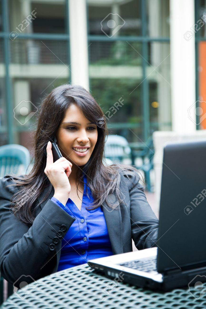 A shot of an indian businesswoman talking on the phone and working on her laptop outdoor Stock Photo - 4913952