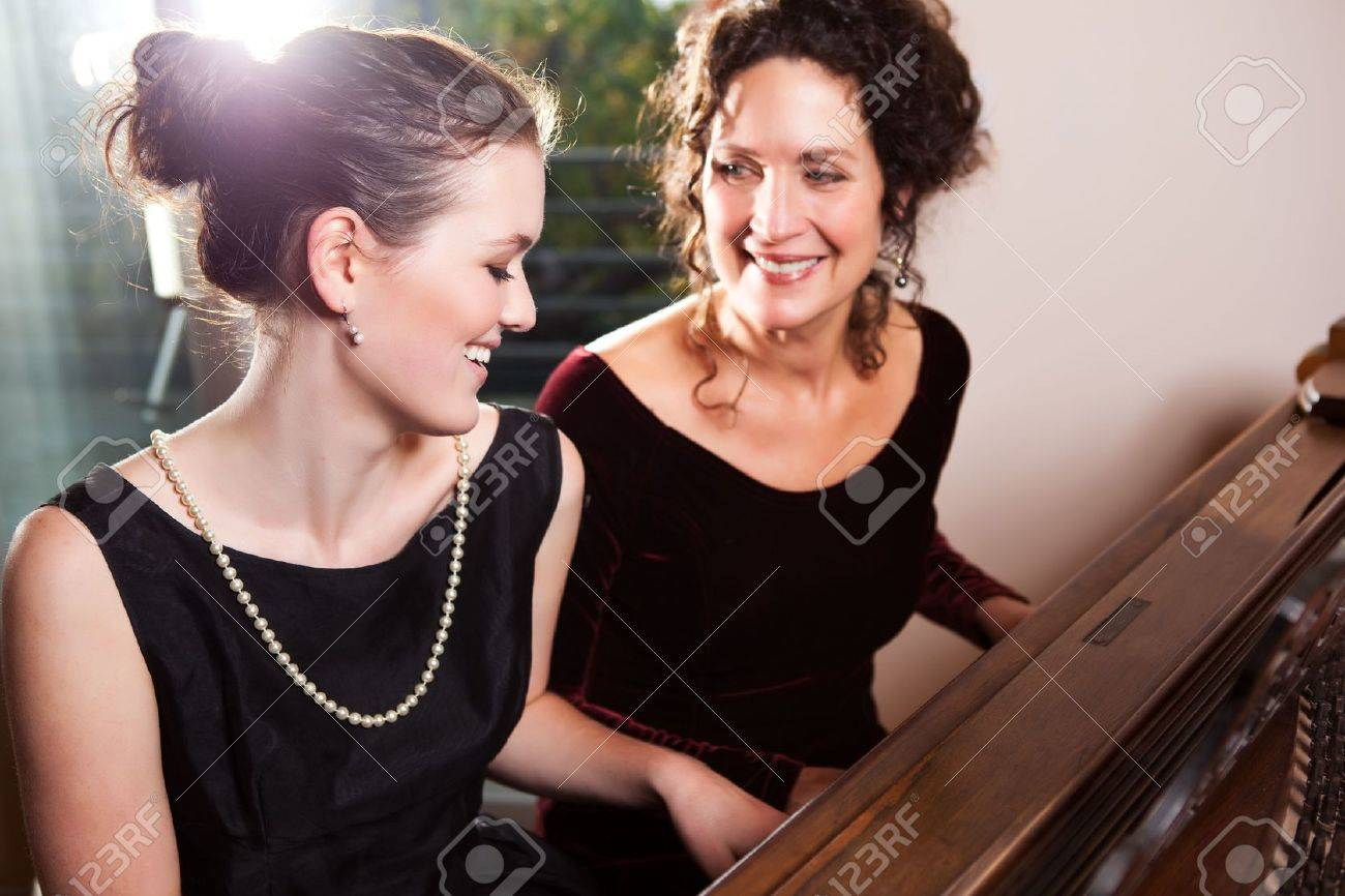 A portrait of a happy mother and daughter playing piano together Stock Photo - 6245845