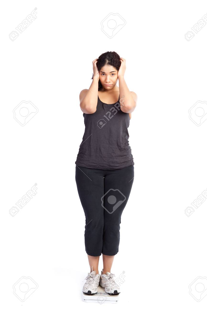 An isolated shot of a unhappy woman standing on a weight scale Stock Photo - 6246009
