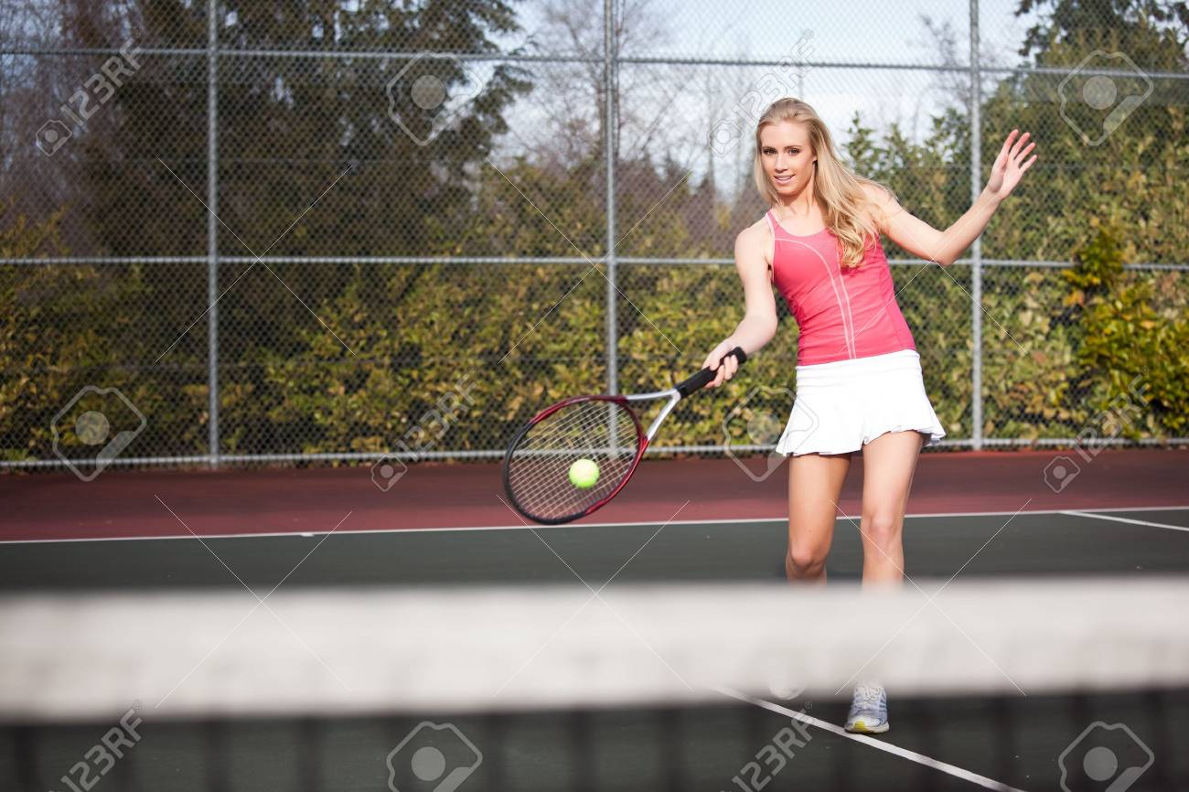 A beautiful caucasian tennis player hitting the ball on the tennis court Stock Photo - 6592633