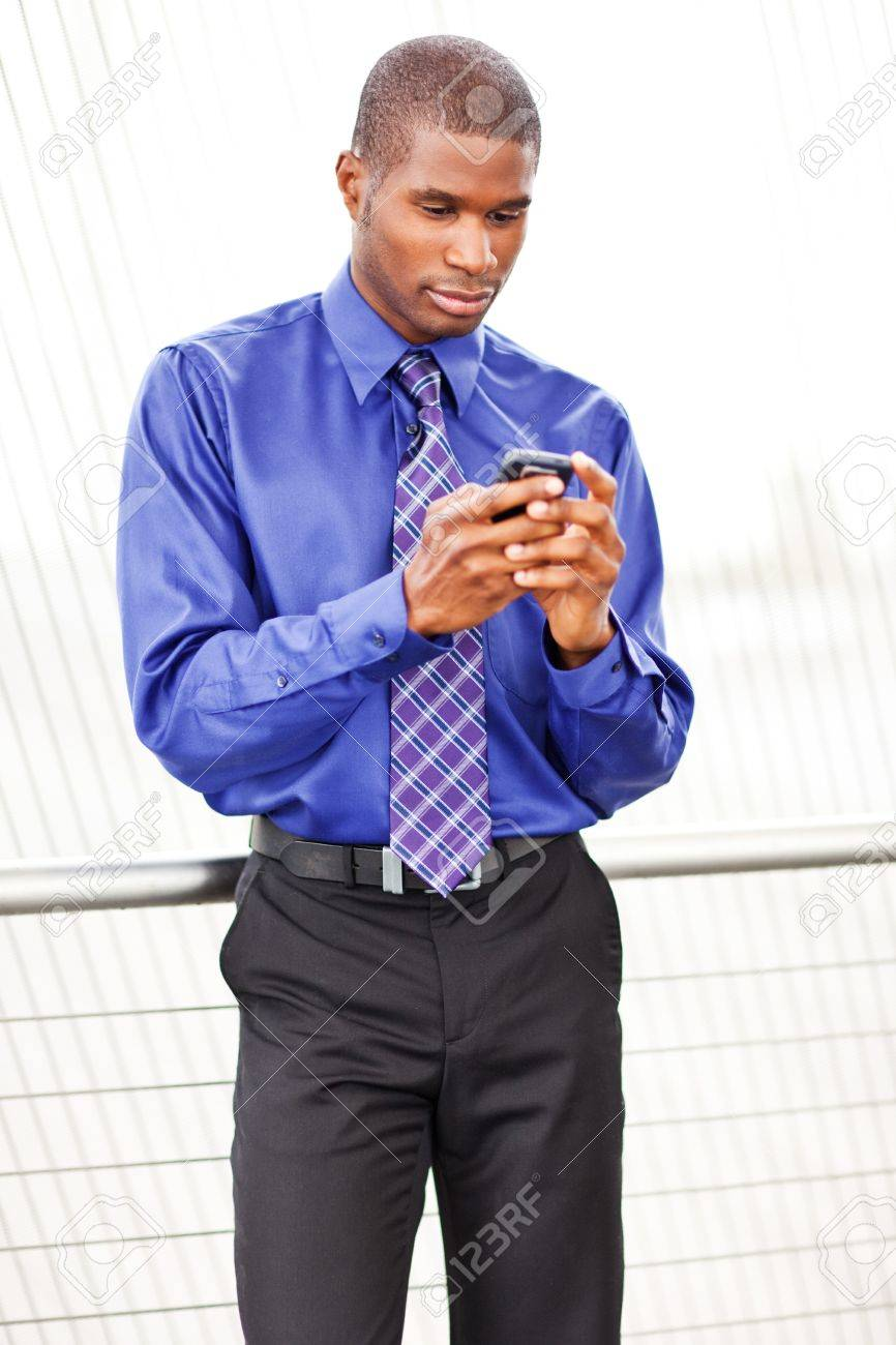 A shot of a black businessman texting Stock Photo - 8066328