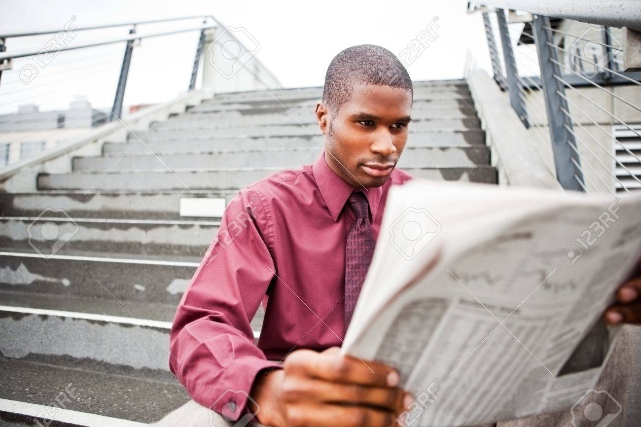 A portrait of a black businessman reading newspaper outdoor Stock Photo - 8066329