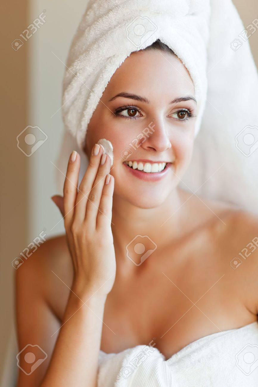 A shot of a young beautiful woman applying lotion to her face Stock Photo - 8205440