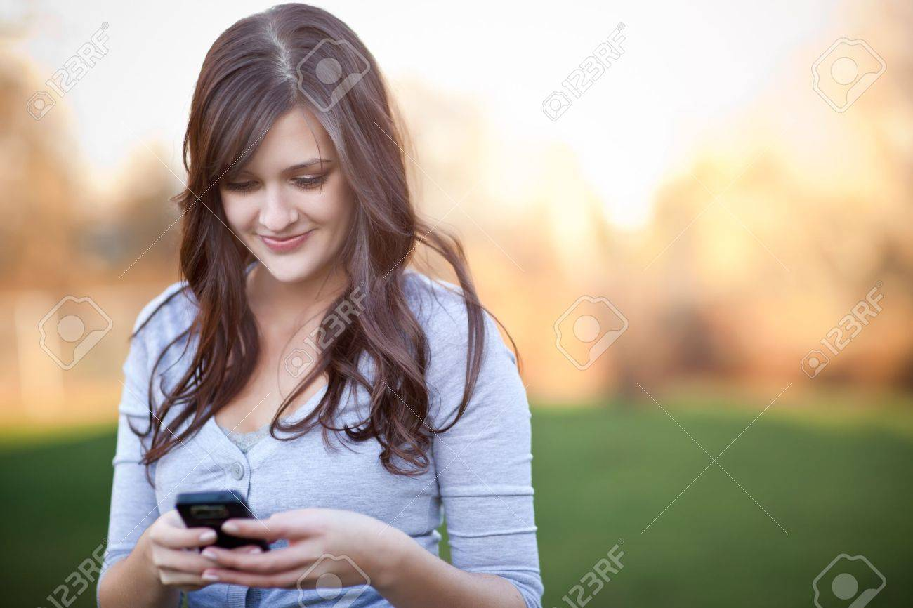 A portrait of a smiling beautiful woman texting with her phone Stock Photo - 8809607