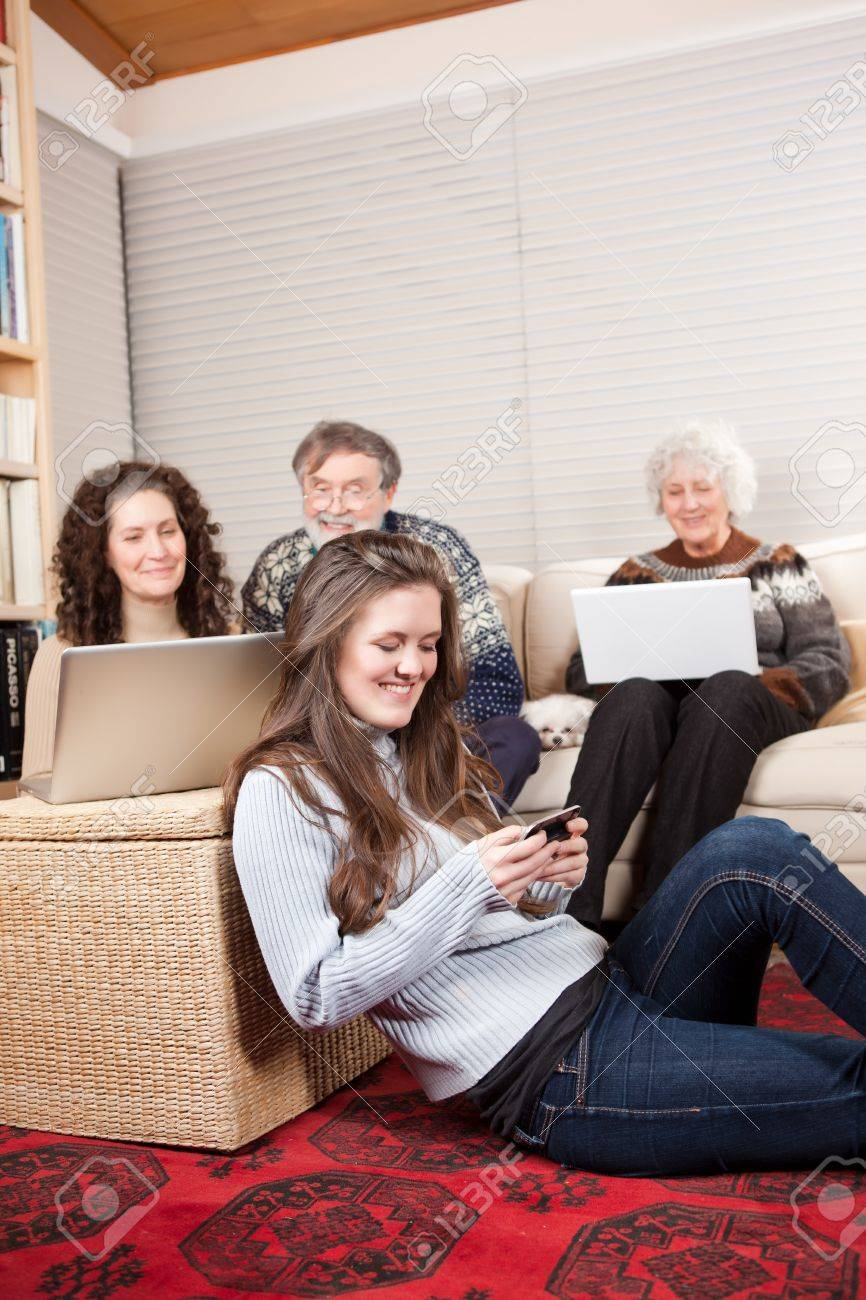 A family at home using wireless technology such as laptop and cell phone Stock Photo - 8929512