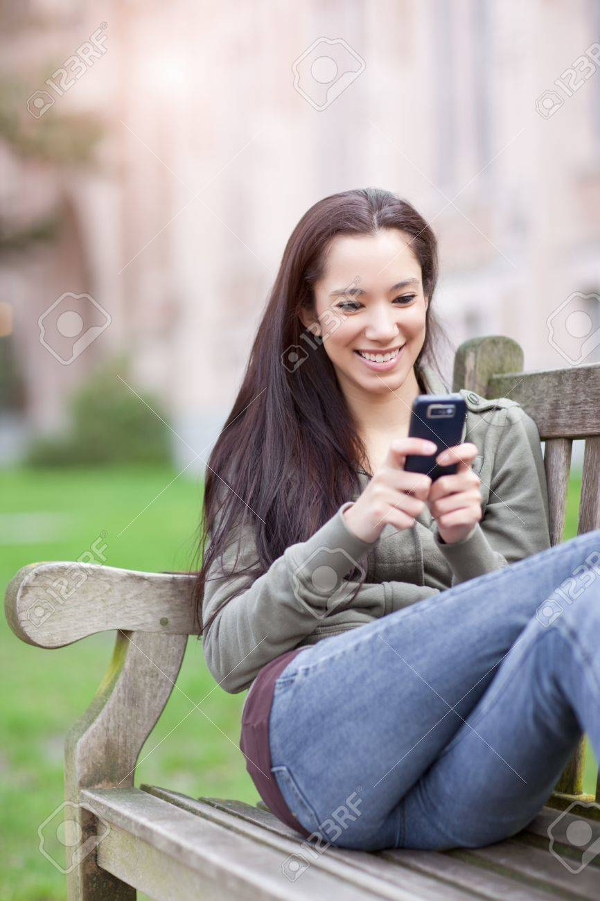 A shot of an ethnic college student texting on the phone at campus Stock Photo - 9154718