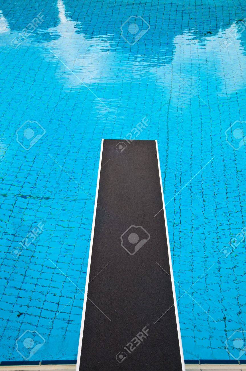 Jumping board in a blue tiled swimming pool