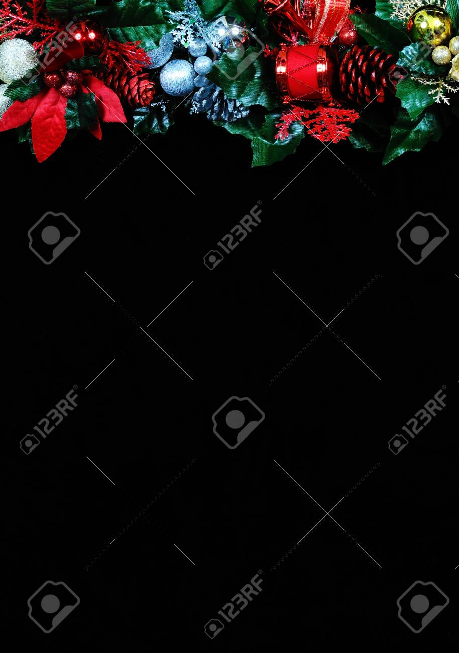 Christmas garland border on the top side of the frame against a black background Stock Photo - 20987112
