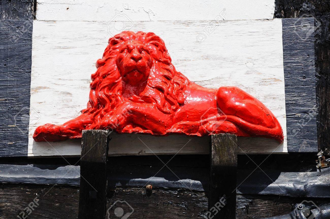 Escultura Del León Rojo En El Lado De Un Edificio Blanco Enmarcado ...