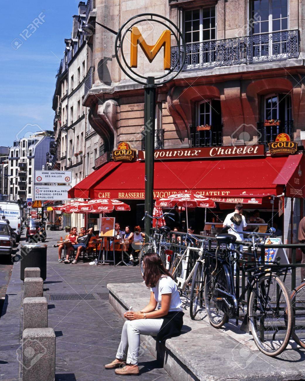 Joven Mujer Sentada Por Un Signo De Metro Con Terraza De Un Café En La Parte Trasera En El Centro De La Ciudad París Francia Europa Occidental