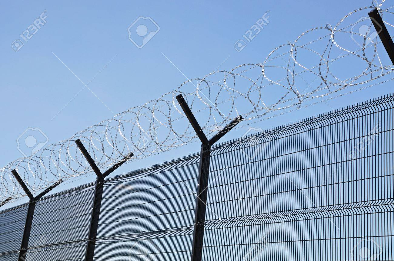 Coiled Barbed Wire On Top Of A Security Fence Stock Photo, Picture ...