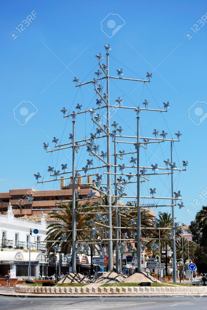 Hundreds Of Windmills On Poles In Centre Of Traffic Island