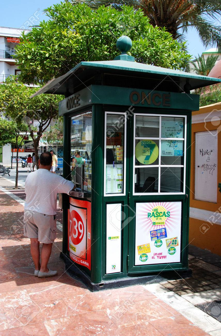 Man standing at a Spanish lottery kiosk in the town centre, Estepona,