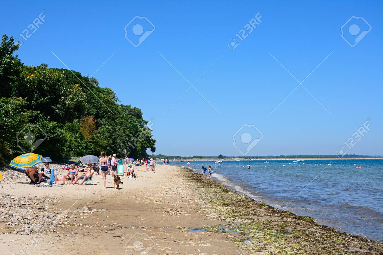 View along the beach with holidaymakers enjoying the Summer sunshine,