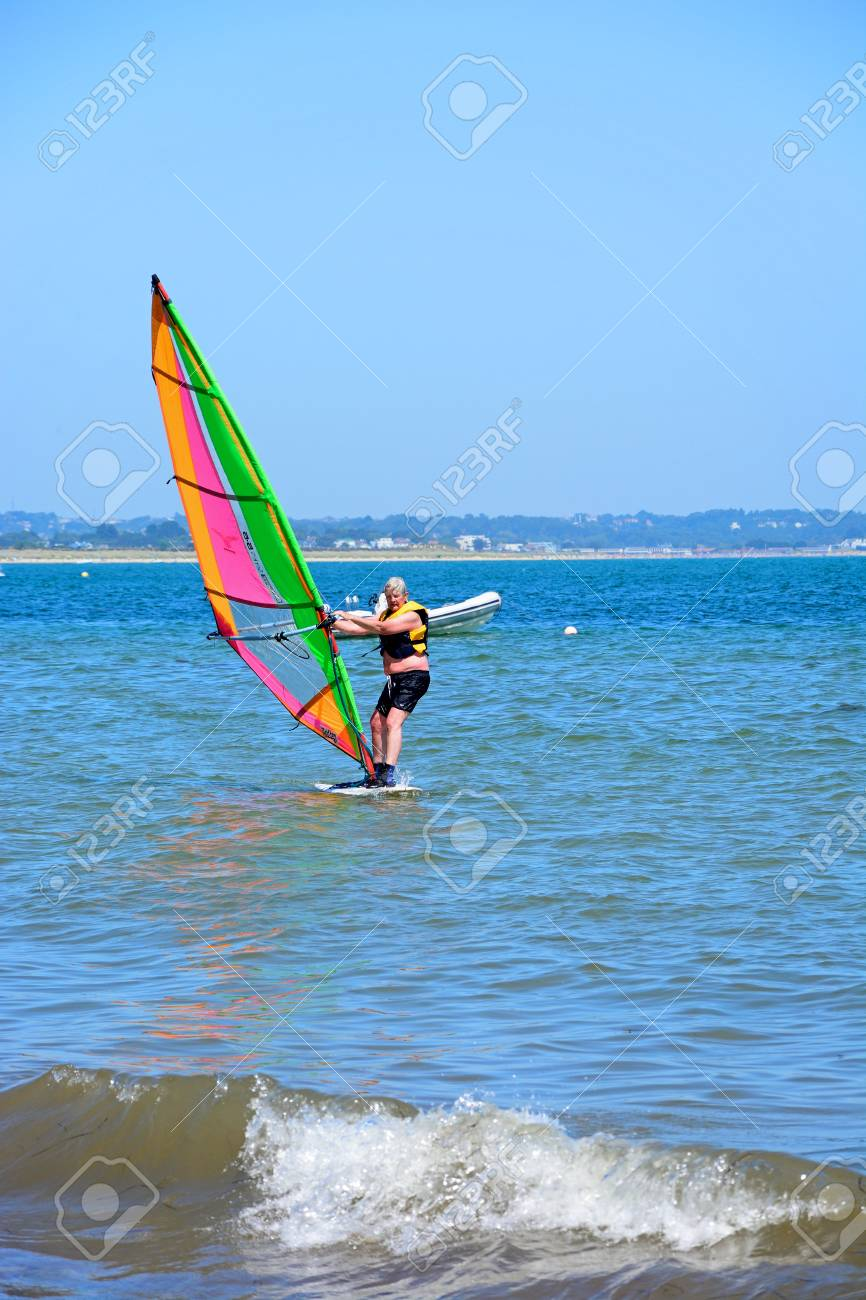 Windsurfer riding the waves near the beach, Studland Bay, Dorset,