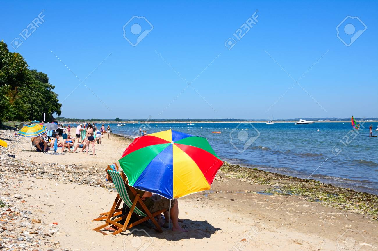 Holidaymakers relaxing on the beach with a colourful parasol