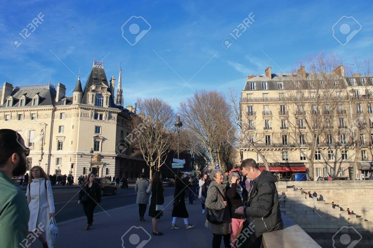 Parisians and tourists strolling on the Saint Michel bridge in Paris, France - 122540126
